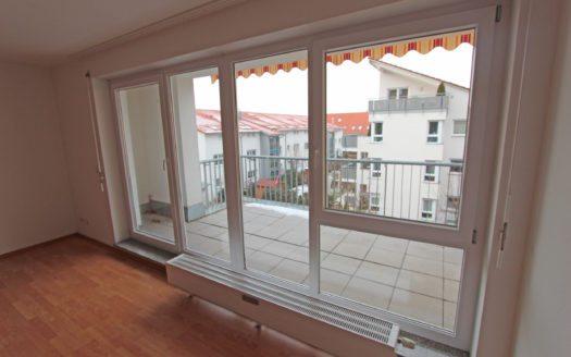 Blick durch Fensterfront auf dahinterliegenden Balkon mit Markise