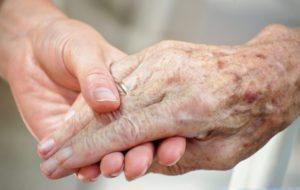 Die Hände eines jungen und eines alten Menschen umfassen einander