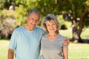 Paar mittleren Alters umarmt sich und lächelt