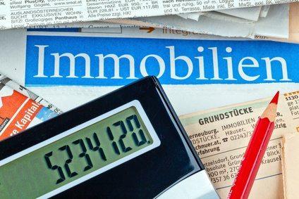Immobilien Inserate in einer Zeitung mit Taschenrechner und rotem Stift