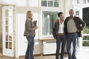 Immobilienmaklerin bei der Besichtigung mit älterem Paar