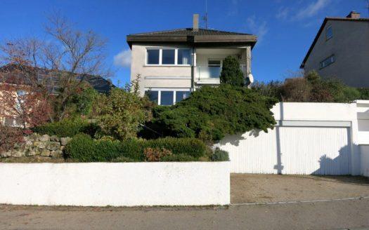 Frontansicht eines Einfamilienhauses mit zwei Garagen und weißer Mauer