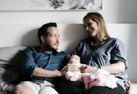 Junges Paar mit Baby in der Mitte lächelt sich an