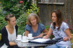 Drei Maklerinnen besprechen die Ereignisse des Tages bei einem Kaffee