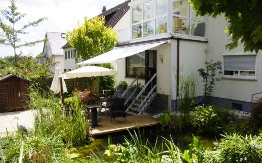 Aussenbereich eines Hauses mit Wintergarten Terrasse und Teich