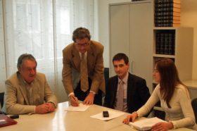 Makler, Käufer und Verkäufer sitzen an Tisch beim Notar