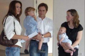 Familie mit zwei Kindern und Maklerin bei der Wohnungsbesichtigung