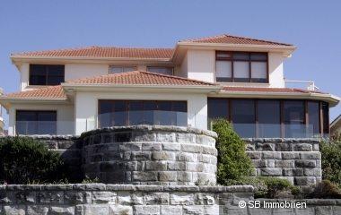 Große Villa mit hohen Fenstern und Steinmauern