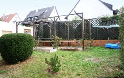 Gartenwiese mit Holzzaunbegrenzung und Häusern im Hintergrund