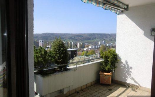 Braun gefliester Balkon mit bunter Markise und kleinem Buxbaum
