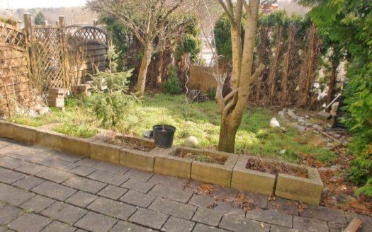 Gepflasterter Vorgarten mit Kübelbeeten und Holzsichtschutz