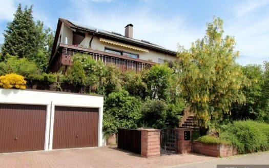 Teilansicht eines Einfamilienhauses mit Holzbalkon und zwei Garagen