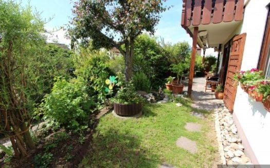 Kleiner Garten und Steinterrasse unter einem Holzbalkon