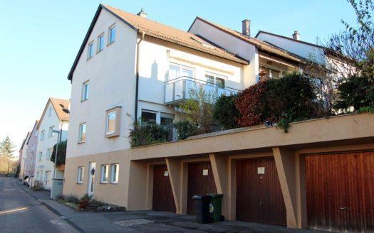 Reihenhaus mit kleinen Fenstern, Balkon und vier Garagen