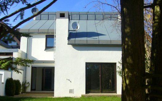Ansicht vom Garten auf Terrasse und Blechdach mit Satellitenschüssel