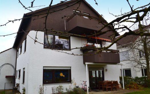 Einfamilienhaus mit braunem Giebel und Balkonen