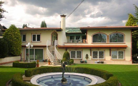 Steinerner Wasserspeier vor toskanischer zweistöckiger Villa