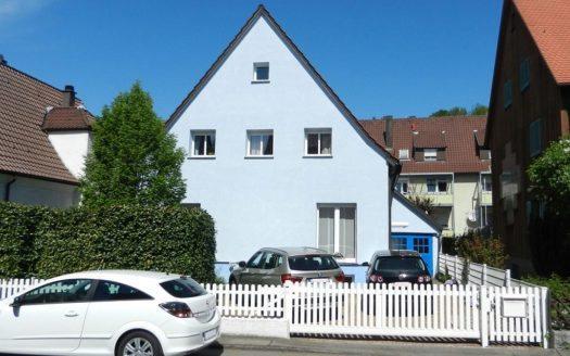 Forntansicht eines hellblauen Einfamilienhauses mit kleinen Fenstern