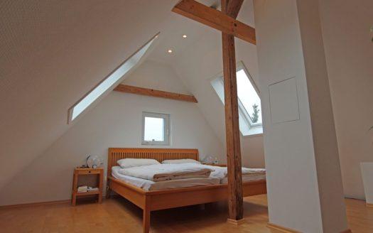 Helles Dachzimmer mit Doppelbett und Holzbalken
