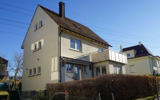 Einfamilienhaus mit Balkon und Hecke