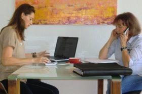 Zwei Frauen an einem Besprechungstisch mit Laptop und Telefon