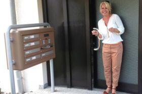 Frau mit strahlendem Lächeln vor Haustüre