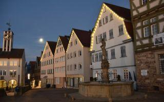 Marktplatz mit Fachwerkhäusern und Brunnen im Mondschein