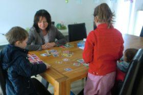 Kinder mit Maklerin beim Memory spielen