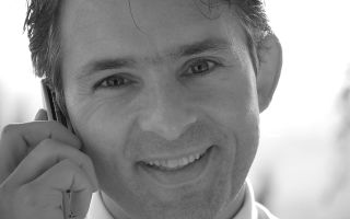 Lächelnder Mann mit Handy am Ohr