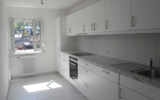 Weiße Einbauküche mit hellem Fliesenboden und mittelgroßem Fenster