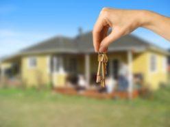 Eine Hand hält einen Schlüsselbund, im Hintergrund steht eine gelbe Villa