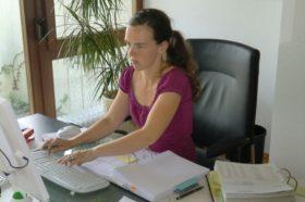 Frau sitzt über Unterlagen an Schreibtisch und tippt auf ihrer Tastatur
