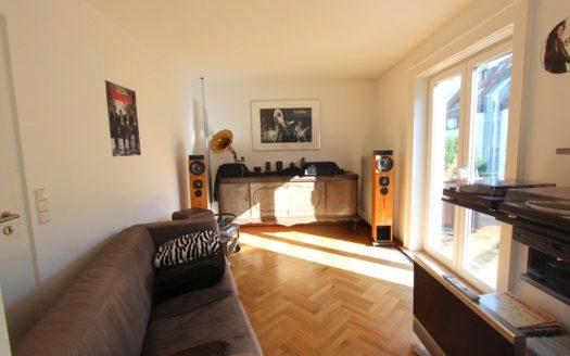 Schmales Wohnzimmer mit Sofa, Plattenspieler und Balkonzugang
