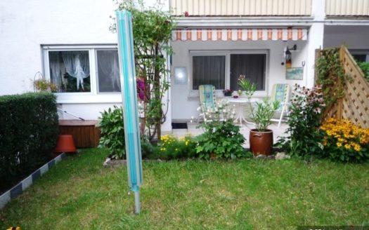 Garten mit Wäschespinne und Blick auf Terrasse mit Markise