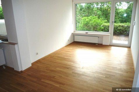 Offener Wohnraum mit Fensterfront und Gartenzugang