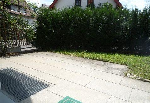 Steinterrasse mit kleinem Rasenstück und Heckenbüsche