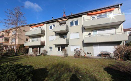 Mehrparteienhaus mit breiten, grau gestrichenen Balkonen