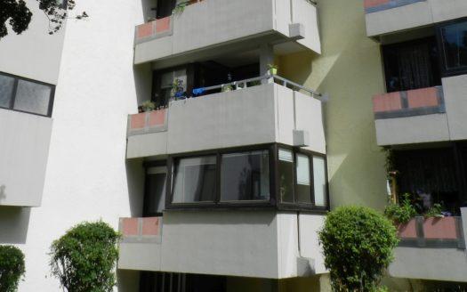 Wohnblock mit mehreren weiß gestrichenen Balkonen