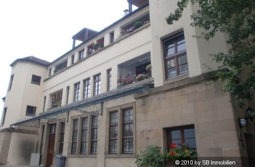 Blick auf älteres Haus mit hohen Gitterfenstern und weißem Turm