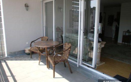 Terasse mit rundem Tisch vor Wohnzimmerzugang