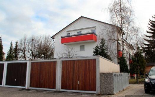 Haus mit drei Garagen und orangefarbenem Balkon
