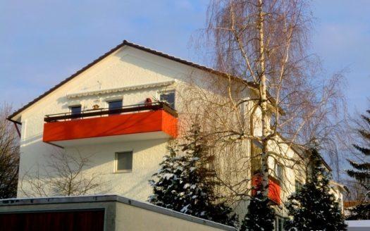 Frontansicht eines weißen Einfamilienhauses mit orangem Balkon