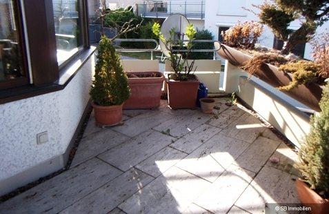 Verwinkelter Steinplattenbalkon mit Kübelpflanzen