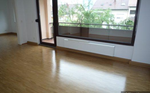 Großes Zimmer mit hellem Parkettboden und Zugang zum Balkon