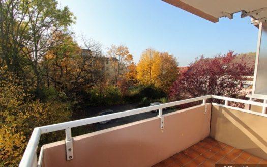 Balkon mit rosa Mauer, im Hintergrund Parkplatz und Bäume