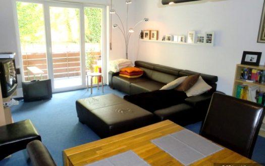 Kombinierter Wohnraum mit schwarzem Ledersofa und Holzesstisch