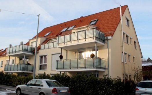 Blick auf Wohnhaus mit breiten Balkonen und rot gedecktem Dach