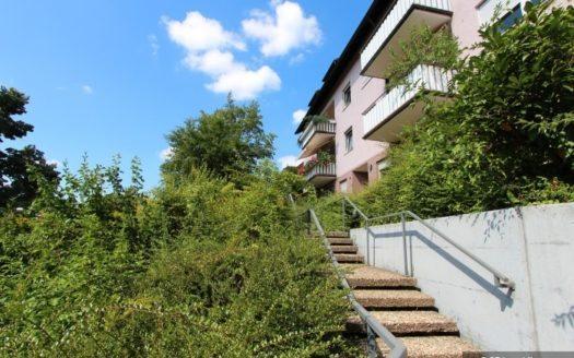 Naturbelassener Garten mit Steintreppe zu lachsfarbenem Mehrfamilienhaus