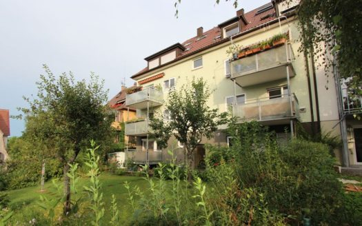 Wohnhaus mit mehreren Balkonen und gepflegtem Garten