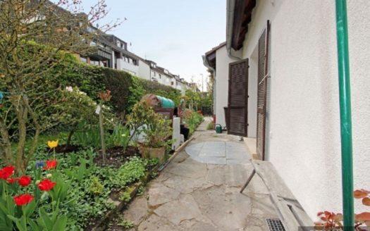 Seitlicher Garten neben gepflastertem Rundweg um Haus